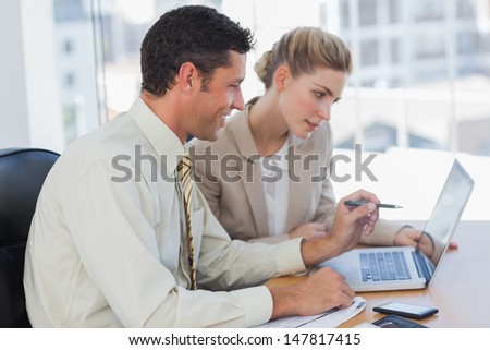 Workmates working together on their computer in their office - stock photo