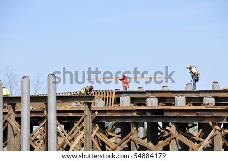 Workmen construct bridge as part of new freeway project - stock photo