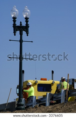 Workmen erect light standard and install guard rails on bridge - stock photo