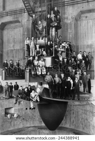 Workmen pose for a group portrait on the giant turbine in the powerhouse of the Bonneville Dam. Ca. 1937. - stock photo
