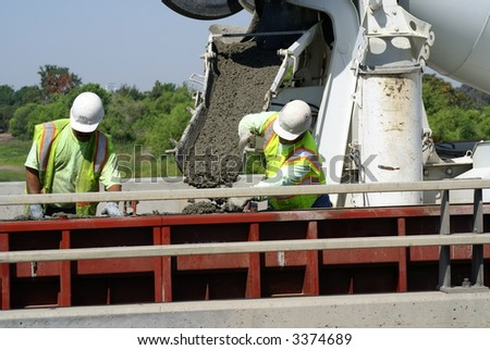 Workmen pour concrete into forms on a bridge construction project - stock photo