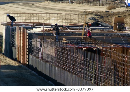 Workmen tie a dense matrix of rebar prior to pouring concrete on a project - stock photo