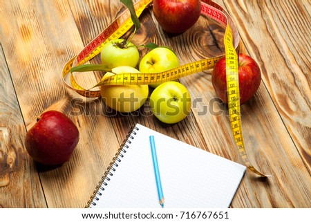 Workout and fitness dieting copy space diary. Healthy lifestyle concept. Apple, dumbbell, and measuring tape on rustic wooden table.