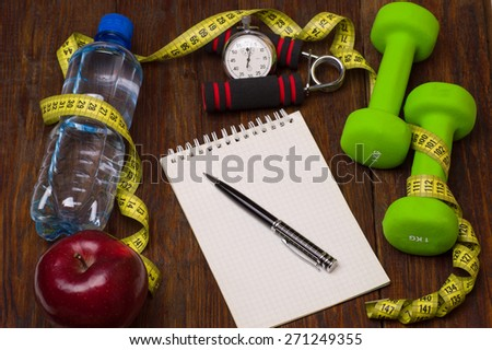 Workout and fitness dieting copy space diary. Healthy lifestyle concept. Apple, dumbbell, water, expander hand, stopwatch and measuring tape on rustic wooden table - stock photo