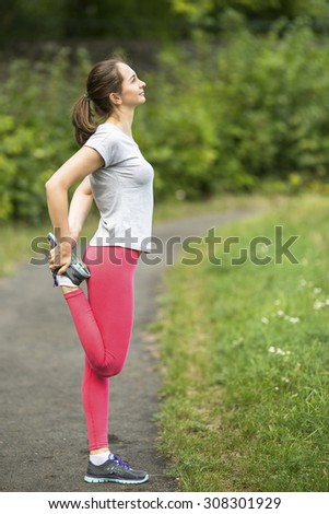 Workout in a Park. Young sporty woman doing exercise warm-up before Jogging in park in sunshine on beautiful summer day. Sport fitness model caucasian ethnicity training outdoors. - stock photo