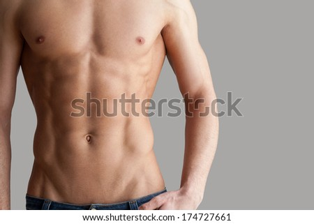 Workout results. Cropped image of muscular man standing isolated on grey background