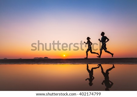 workout, silhouettes of two runners on the beach at sunset, sport and healthy lifestyle background - stock photo