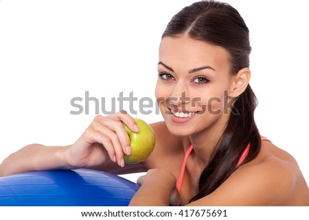 Workout snack. Cropped shot of a young attractive woman sitting next to her fitness ball and eating an apple. - stock photo