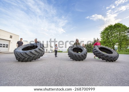 Workout team flipping heavy tires outdoor - stock photo