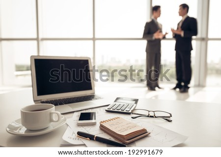Workplace and businesspeople on background - stock photo