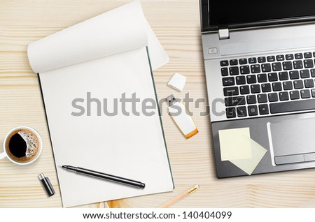 Workplace, laptop and notepad on wooden table - stock photo