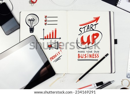 Workplace. Notepad with  Start Up lettering on table with tablet pc, mobile phone. - stock photo
