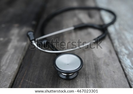 Workplace of a doctor. Stethoscope on wooden or vintage desk background. selective focus