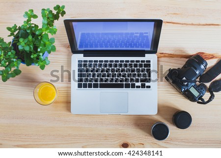 workplace of photographer, top view of gear, camera with lenses and laptop computer - stock photo