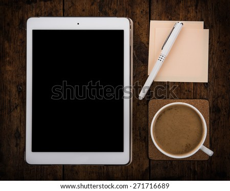 workplace, office desk: cap of coffee and tablet pc and notebook with pen - stock photo