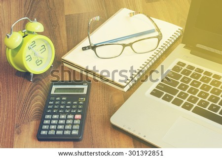 Workplace on wood table : laptop, documents, calculator, glasses and clock - stock photo