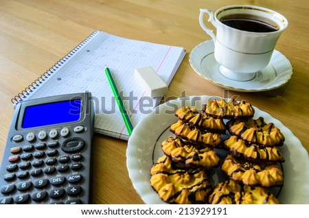 workplace, study place with calculator (with blue box), workbook, cup of coffee and cookies - stock photo - stock photo