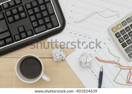 Workplace with keyboard, graph, calculator, pan, and coffee on wood table.