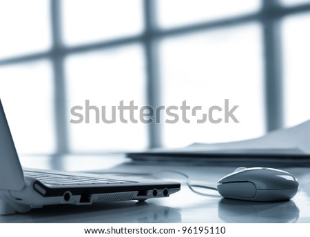 Workplace with laptop and  mouse on  background of window - stock photo