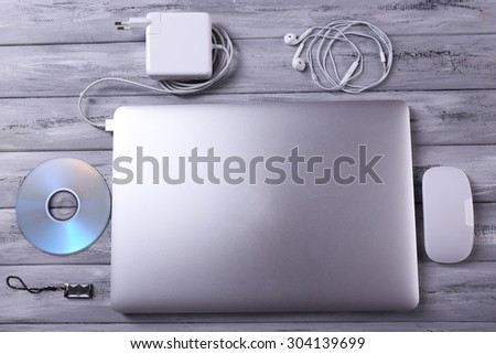 Workplace with laptop and other computer accessories on wooden background - stock photo