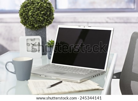 Workplace with laptop computer, coffee, pen and newspaper. - stock photo