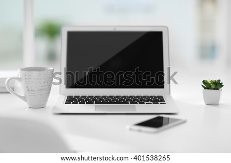 Workplace with laptop, mobile phone and cup of coffee indoors - stock photo
