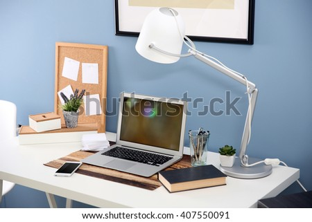 Workplace with laptop, mobile phone and table on blue wall background - stock photo