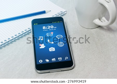 Workplace with mobile phone on table close-up - stock photo