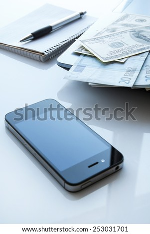 Workplace with money and electronic devices - stock photo