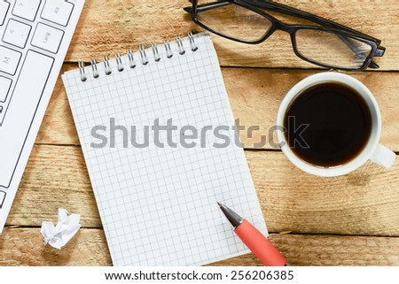 Workplace with notebook and coffee. Workplace with keyboard , coffee, notebook with pen on wood table - stock photo