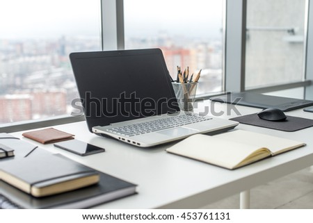 Workplace with notebook laptop Comfortable work table in office with windows and city view - stock photo