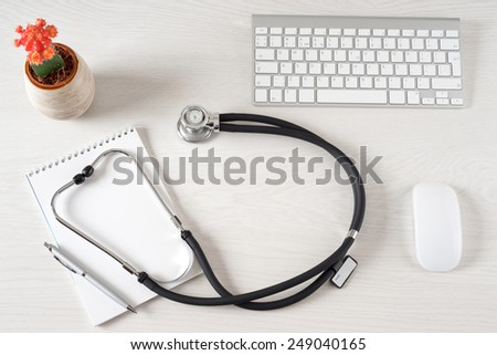 Workplace with notepad and keyboard, and stethoscope - stock photo
