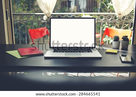 Workplace with open computer, colorful notebooks and stickers, laptop with blank copy space empty screen for your content or text message, modern table at open window in home interior in summer,filter - stock photo