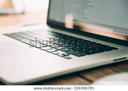 Workplace with open laptop on modern wooden desk, angled notebook on table in home interior, filtered image, soft focus - stock photo