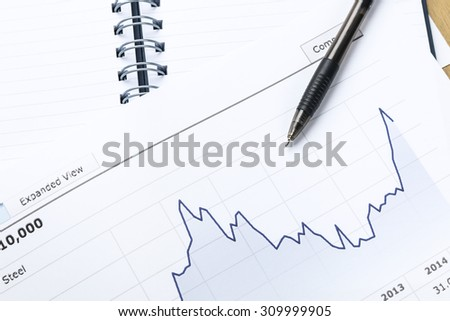 workplace with pen, notebook, financial report in concept of business and financial  - stock photo