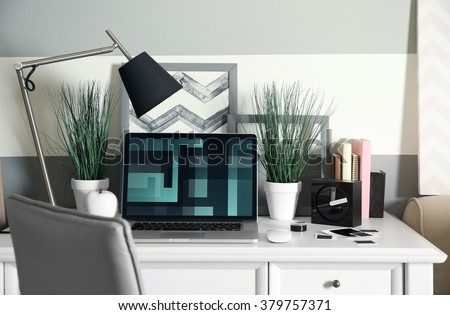 Workplace with table, lamp and laptop in living room - stock photo