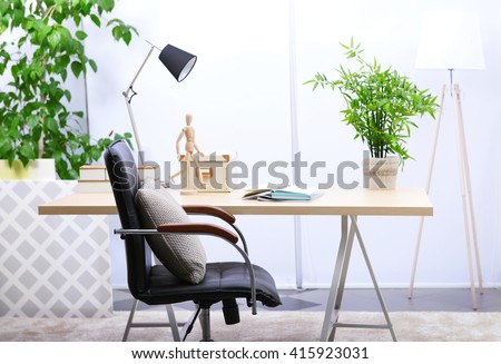 Workplace with table, office chair and lamp in living room - stock photo