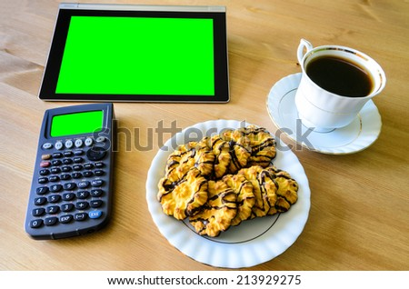 workplace with tablet pc - green box, calculator, cup of coffee and cookies - stock photo - stock photo