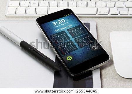 Workplace with tablet pc showing calendar on work table close-up - stock photo