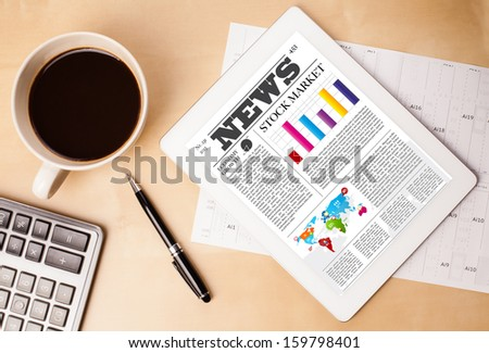 Workplace with tablet pc showing latest news and a cup of coffee on a wooden work table close-up - stock photo