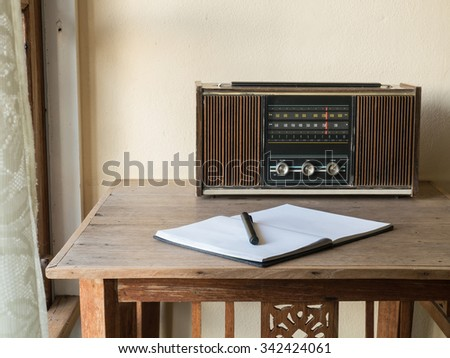 Workplace with vintage retro radio, notebook and pen on wooden table