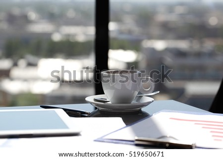 Workplacxe with coffee, financial reports and tablet pc near window with view at cityscape