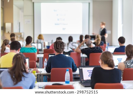 Workshop at university. Rear view of students sitting and listening in lecture hall doing practical tasks on their laptops. Copy space on white screen. - stock photo