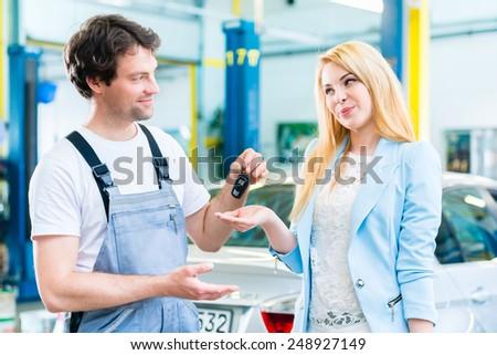 Workshop mechanic handing car to customer - stock photo