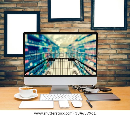workspace on brick wall background with advertise frame show Abstract blurred photo of store with trolley in department store bokeh background, online shopping concept - stock photo