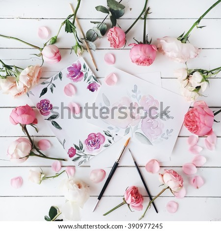 Workspace. Pink and red roses painted with watercolor, paintbrush and roses on white wooden background. Overhead view. Flat lay, top view - stock photo