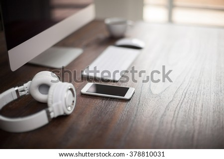 Workspace with a desktop computer, headphones and a smartphone on a wooden table with very shallow dept of field and plenty of copy space - stock photo