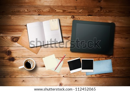 Workspace with coffee cup,  tablet pc, instant photos, note paper and notebook on old wooden table - stock photo