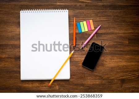 Workspace with colored pencils and notebook on old wooden table - stock photo