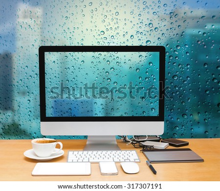 Workspace with computer desktop on the wood table with a glass surface windows with cityscape background - stock photo